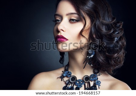 Close-up studio portrait of beautiful woman. Beautiful brunette model with long curly brown hair.