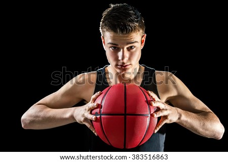 Close up studio portrait of handsome young basketball player holding inflated orange ball.Isolated against black background.