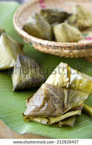close up stuffed dough pyramid dessert on banana leaf