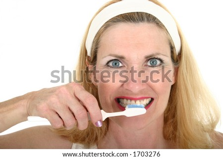 Close-up view of a beautiful middle-aged woman brusing her teeth.  Shot isolated on white background.