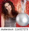 Close up view of an attractive young woman holding a large christmas tree bar ball in the air while standing in front of a red glitter background smiling. - stock photo