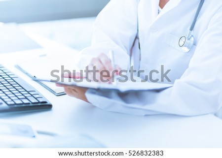 Close-up view of female doctor hands filling patient registration form. Healthcare and medical concept