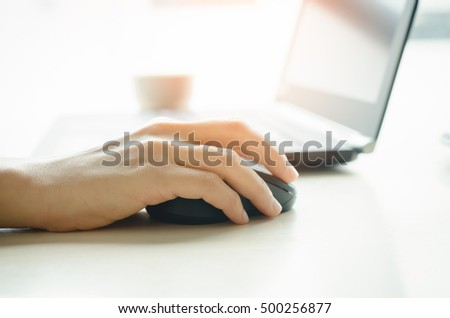 Close up woman hand using mouse and notebook background. Technology and business concept. Shallow depth of field. Vintage tone filter color style.