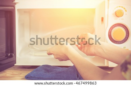 Close up woman hand with microfiber cleaning rag wiping inside of microwave oven.