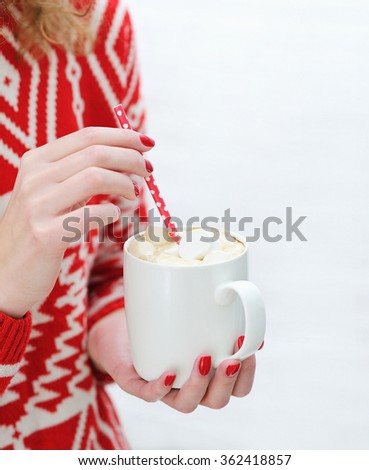 Close up woman hands with bright red manicure nails design holding cozy knitted mug with marshmallow hot chocolate. Winter and Christmas time concept