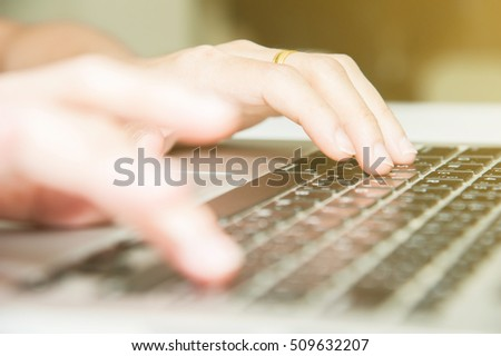 Close view finger press button on laptop keyboard with gold light