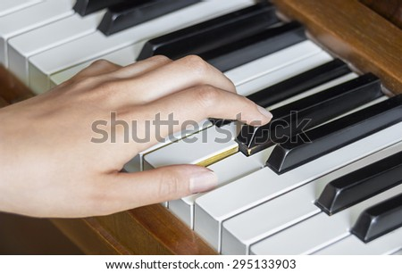 Close view of  girl's left hand holding pressed  keys on a piano