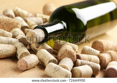 Closed wine bottle and heap of used corks on wooden surface.