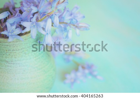 Closeup Aerial of Dreamy Pastel Lavender Lilly Flowers Spilling out of a Green Stoneware Vase with a Teal Blue Horizontal Wood Background with room or space for copy, text, your words to the side