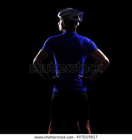 Closeup back view of a cyclist in a black studio