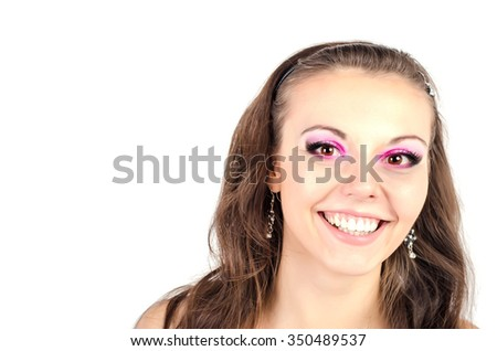 Closeup beauty portrait of attractive model face with bright visage. Chic pink eye makeup. Brown eyes. Happy smiling. Isolated on white