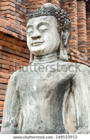 Closeup Buddha statue on brick wall in Temple, Thailand