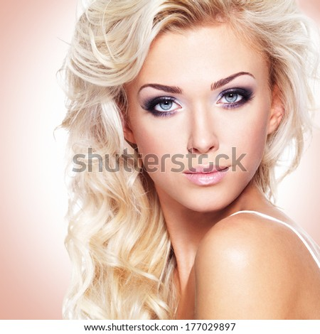 Closeup face of a beautiful woman with long white curly hair. Portrait of fashion model with bright makeup at  studio