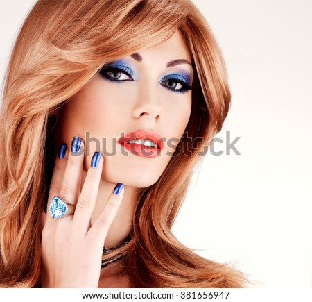 Closeup face of a sensual beautiful woman with blue nails, blue makeup and sexy red lips  on white  background