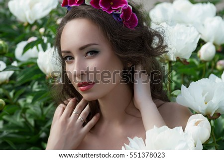 Closeup face of young woman with white peonies