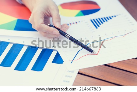 Closeup female hands pointing with pen at business document, financial report while discussing company profit growth. Businesspeople, stockholders meeting in corporate office, concept. Wall street