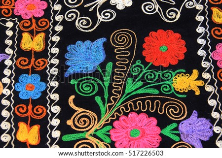 closeup fragment of multi-colored floral embroidery on black fabric