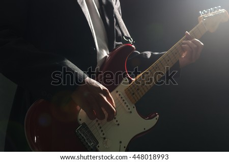 Closeup musician playing the guitar on dark background with lens flare from spot light, musical concept