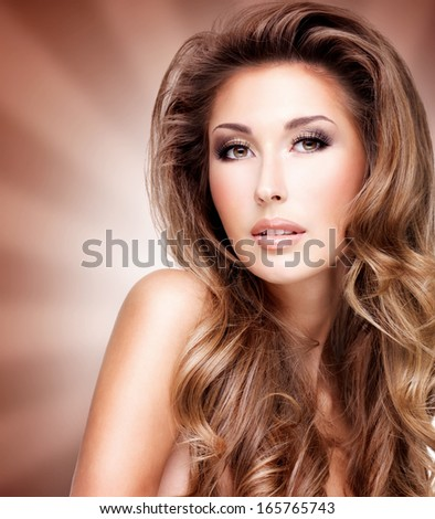 Closeup of a beautiful woman with wavy long hair. Fashion model posing at studio over art background