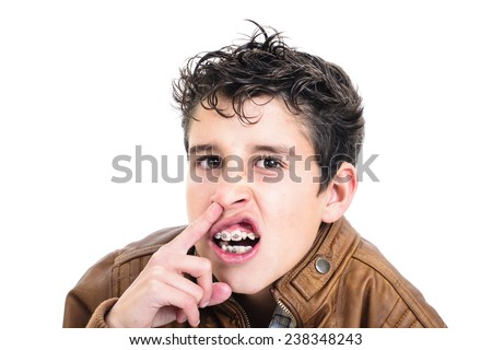 Closeup of a boy with his finger in the nose with braces