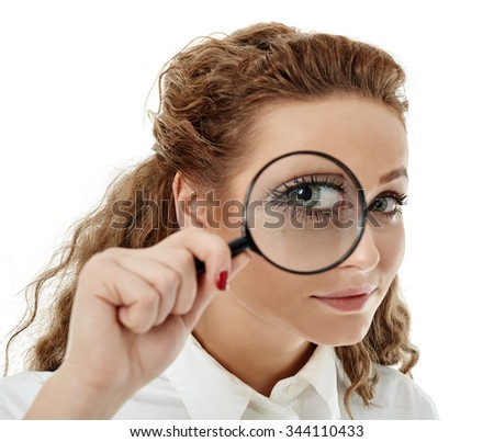 Closeup of a business woman looking at camera through a magnifier