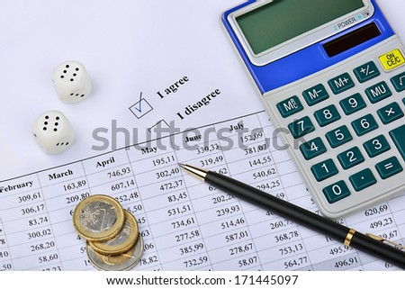 Closeup of a calculator, financial chart, coins, dice, pen and I agree-option.