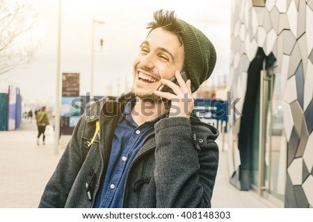 closeup of a caucasian and young man while he is speaking and smiling, at the his smart phone - lifestyle, people and technology concept