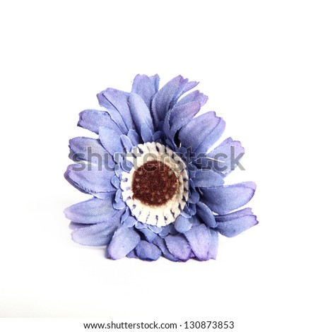 Closeup of a decorative blue flower lying on a white background