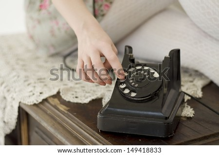 closeup of a girl's hand dialing the number on an old phone