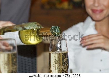 Closeup of a man pouring white wine in a glass. Restaurant, room service, a holiday.  Selective focus, blur