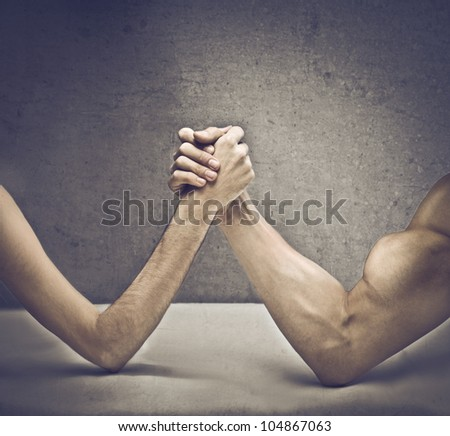 Closeup of a muscular man playing arm wrestling with a skinny one