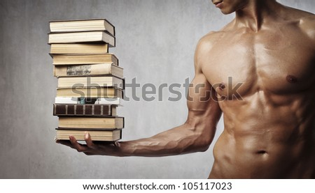 Closeup of a muscular young man holding a stack of books on one hand