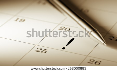 Closeup of a personal agenda, organizer or planner, setting an important date with a Ballpoint pen marking a day of the month representing a organizing time and schedule.