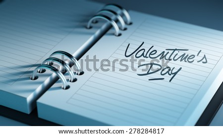 Closeup of a personal agenda setting an important date representing a time schedule. The words Valentine's Day written on a white notebook to remind you an important appointment.
