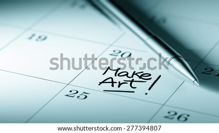 Closeup of a personal agenda setting an important date written with pen. The words Make Art written on a white notebook to remind you an important appointment.