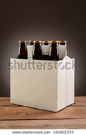 Closeup of a six pack of brown beer bottles on a rustic wooden table. Vertical format with a light to dark gray spot background.