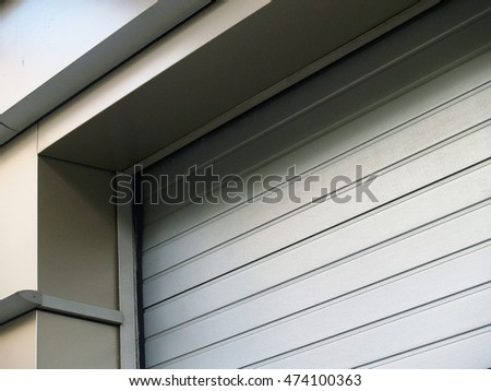 Closeup of a surface of gray metal roller gates with aluminum siding shutter. Abstract geometry composition
