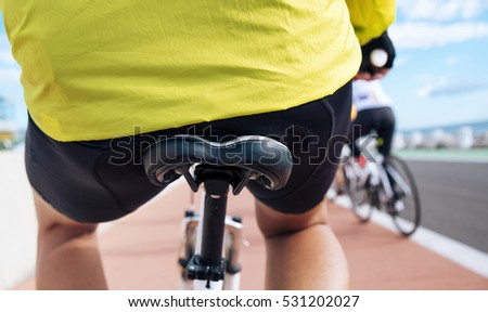 closeup of a young caucasian man wearing sport clothes seen from behind riding his bicycle by a bike lane next to the ocean