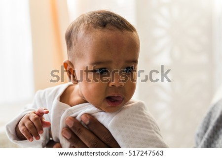 Closeup of African American curious baby boy looking away