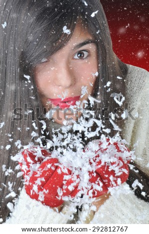 Closeup of an attractive brunette girl blowing snow out of her hands against a light to dark red background. The girl is wearing red gloves and a white sweater.