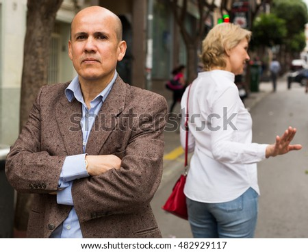 closeup of angry retiree man being sad with woman standing outdoors