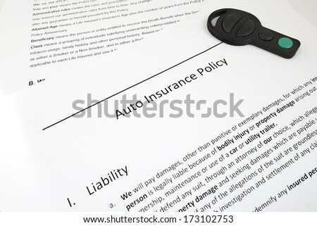 Closeup of auto insurance policy with car key