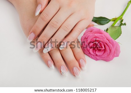 Closeup of beautiful nails with french and pink flower on white background
