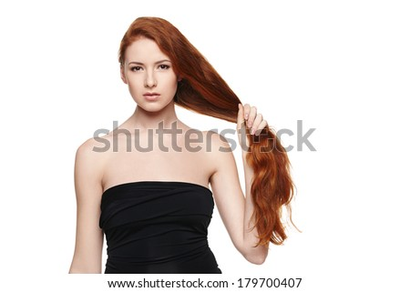 Closeup of beautiful redheaded woman holding her hair in the hand over white background