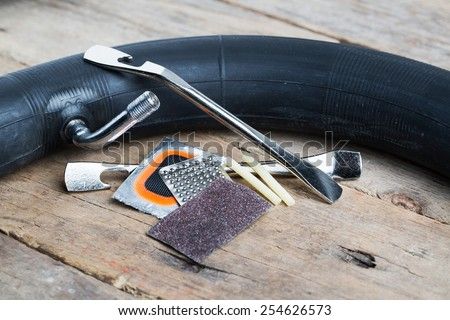 Closeup of bike tire repair kit on wooden table
