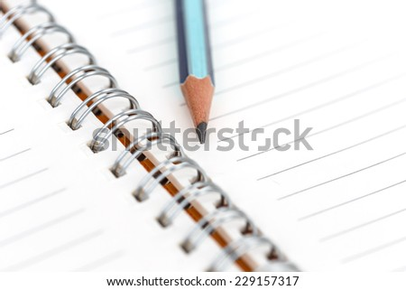 closeup of blank notebook and pencil for text or background