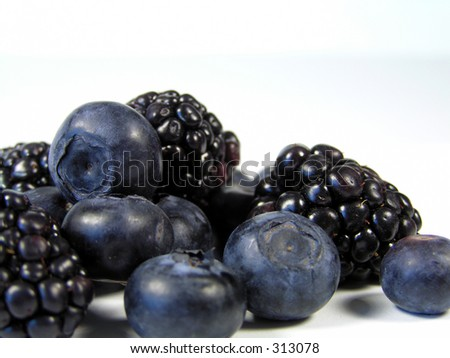 closeup of blueberries and blackberries isolated on white in a pile