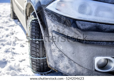 Closeup of car tire with mounted snow chains in winter season