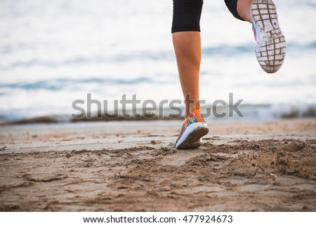 Closeup of female legs in sportswear running on beach at sunset in morning. Fitness, workout and healthy lifestyle concept. Blue sky with clouds and sea on background