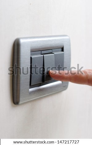 Closeup of finger pressing light switch on the wall, turning lights on or off